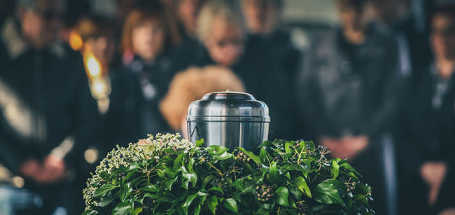funeral urn next to mourners