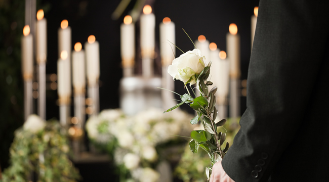 funeral candles next to a person holding flowers